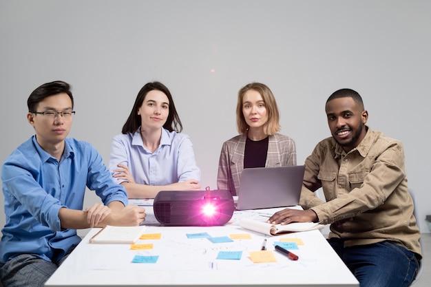 Retrato de jovens especialistas inter-raciais sentados à mesa com um projetor e assistindo à apresentação na reunião