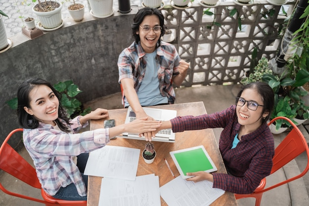 Retrato de jovens estudantes asiáticos se encontrando em um café fazendo high five juntos