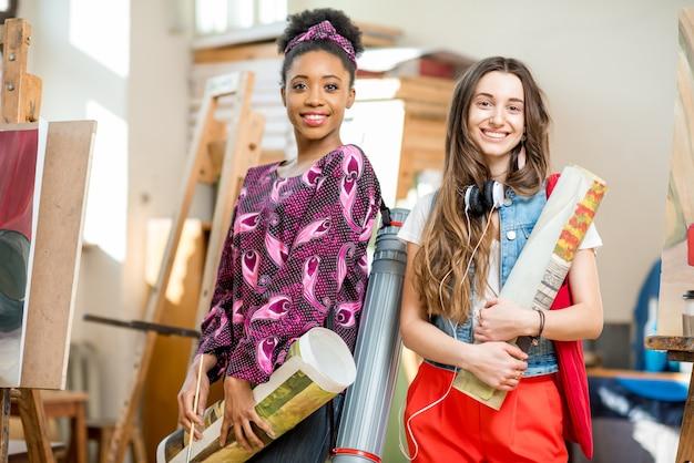 Retrato de jovens estudantes criativos de várias etnias em pé junto com pinturas no estúdio da universidade para pintar