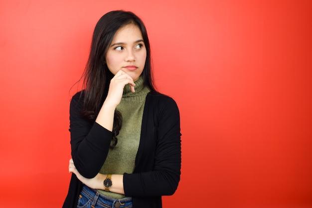 Retrato de jovens lindas mulheres asiáticas usando suéter preto gesto de pensamento isolado no vermelho