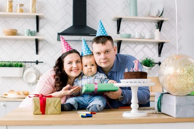 Retrato de jovens pais felizes comemorando o primeiro aniversário do seu filho em casa
