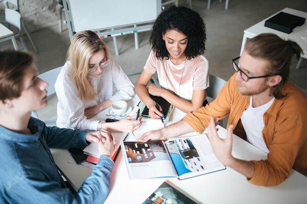 Retrato de jovens sentados no escritório, discutindo algo. grupo de caras legais trabalhando em um novo projeto enquanto está sentado em um café