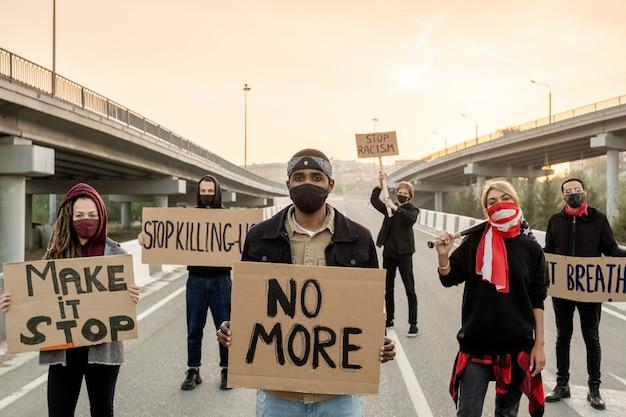 Retrato de jovens sérios insatisfeitos com máscaras em pé com cartazes e participando de manifestação