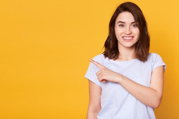 Retrato de linda alegre garota alegre apontando para o lado com o dedo indicador