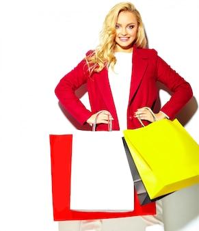 Retrato de linda feliz doce doce mulher loira sorridente segurando nas mãos grandes sacos de compras