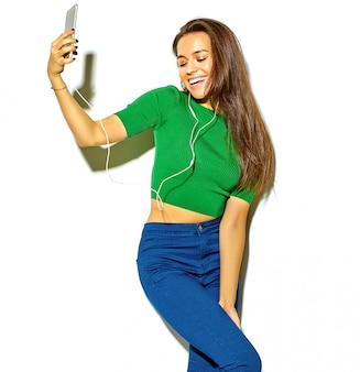 Retrato de linda feliz sorridente mulher morena menina bonita em roupas de verão casual hipster verde sem maquiagem isolada no branco, tire uma selfie