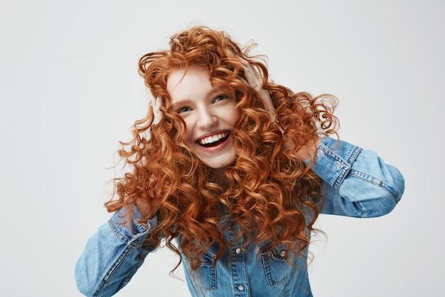 Retrato de linda garota feliz sorrindo tocando seu cabelo ruivo cacheado.