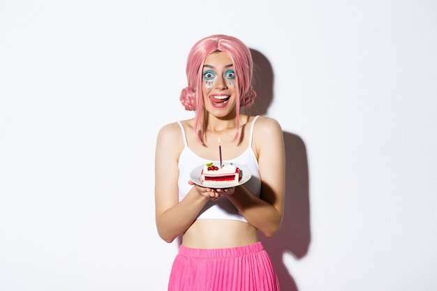 Retrato de linda garota lambendo os lábios segurando um bolo delicioso, comemorando o aniversário, vestindo peruca rosa e fantasia brilhante para a festa.