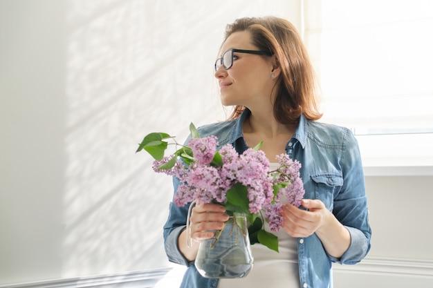 Retrato de linda mulher madura em casa com buquê de lilás