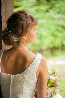 Retrato de linda noiva em estilo rústico. penteado de noiva. detalhe do laço do vestido de noiva em marfim vista de perto. vestido de noiva com cordões em marfim com cristais e brilhantes. pedaço de tecido de renda de casamento branco