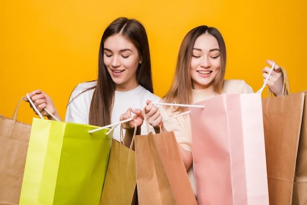 Retrato de lindas garotas bonitas abraçando, segurando nas mãos, carregando uma nova compra legal isolada na parede amarela