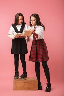 Retrato de lindas garotas em uniforme escolar lendo livros, em pé, isolado na parede vermelha