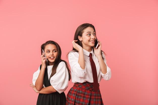 Retrato de lindas garotas em uniforme escolar usando telefones celulares para fazer chamadas, em pé isolado na parede vermelha