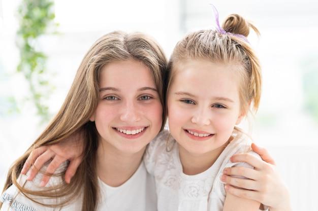 Retrato de lindas irmãs sorridentes se abraçando dentro de casa