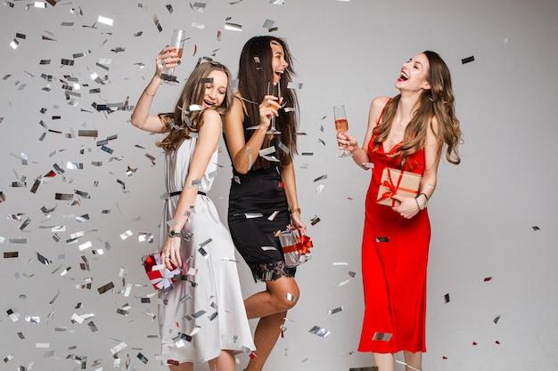 Retrato de lindas mulheres joviais e despreocupadas em vestidos de coquetel com copos de bebidas alcoólicas, dançando e se divertindo sob confetes prateados caindo
