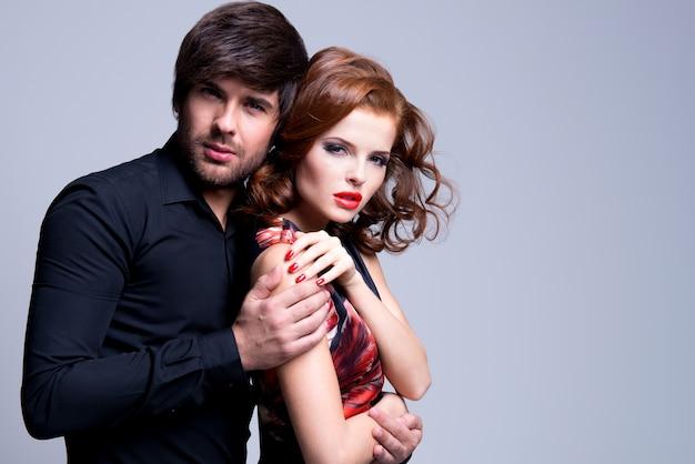 Retrato de lindo casal apaixonado e apaixonado, abraçado em um fundo cinza