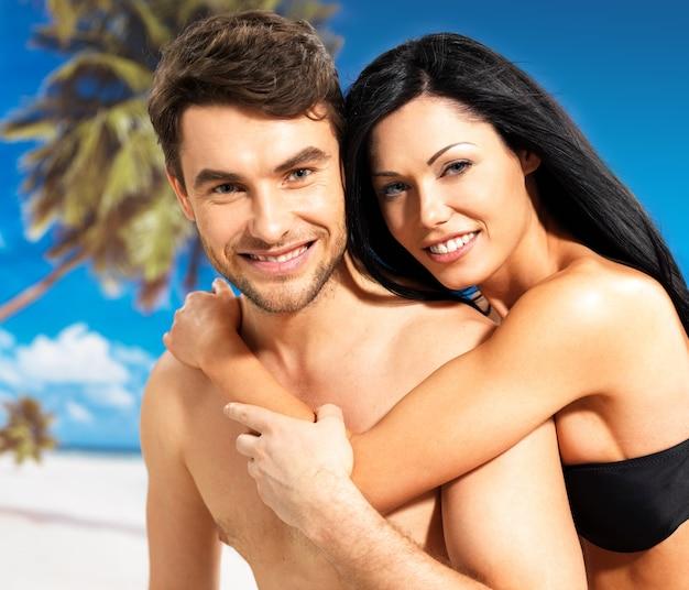 Retrato de lindo casal apaixonado e sorridente feliz em uma praia tropical