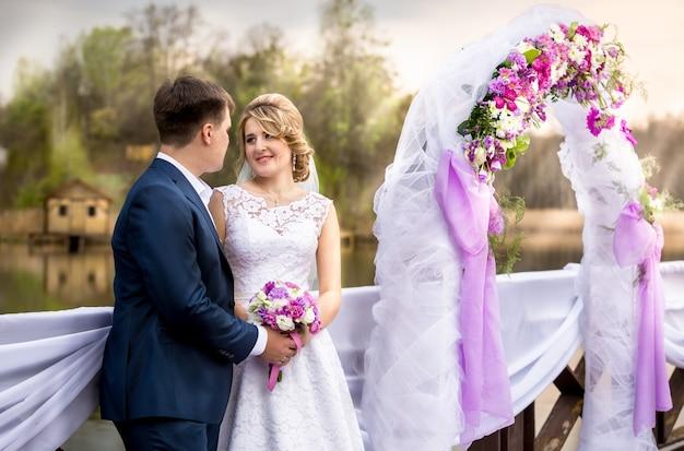 Retrato de lindos recém-casados sorridentes posando em arco floral ao pôr do sol