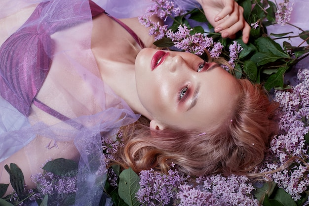 Retrato de loira sexy em lingerie com maquiagem brilhante, deitado na flor lilás.