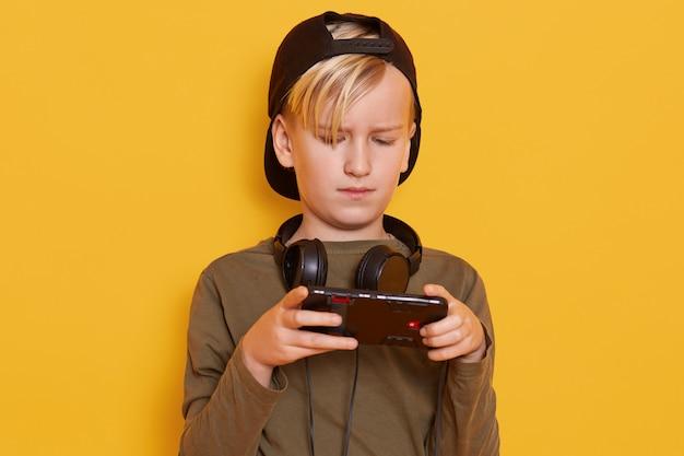 Retrato de loiro bonitinho, tendo olhar sério e concentrado enquanto estiver usando telefone celular, garoto jogando videogame on-line