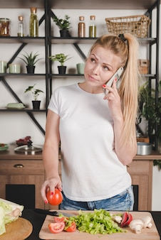 Retrato, de, loiro, mulher jovem, falando, ligado, móvel, ficar, em, cozinha