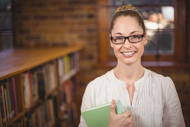 Retrato, de, loiro, professor, segurando, livro, em, a, biblioteca, em, escola