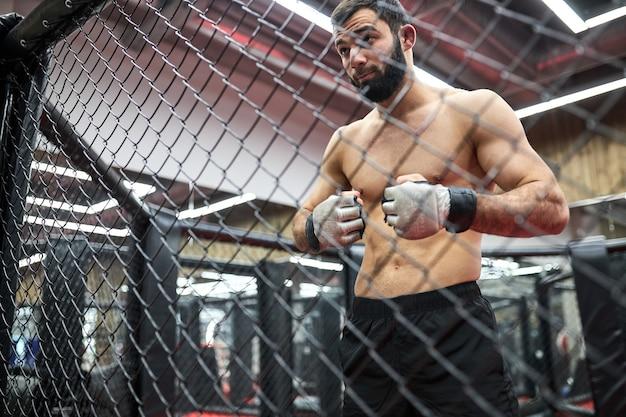 Retrato de lutador de mma pensando em estratégia para a luta, em pé no ringue se preparando para a luta, homem musculoso sem camisa vai praticar luta. atirado através da gaiola