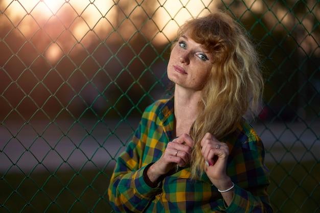 Retrato de luz do sol de ruiva ruiva weared em camisa xadrez atrás da cerca