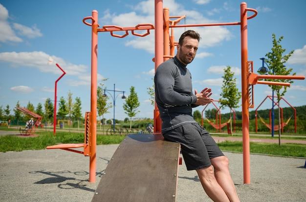 Retrato de macho bonito, homem atraente e esportivo, atleta europeu de construção muscular caucasiana, olhando para a câmera no fundo de barras transversais e máquinas de ginástica em esportes ao ar livre de verão