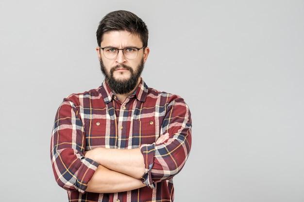 Retrato de macho europeu determinado infeliz com olhar sério e preocupado contra cinza