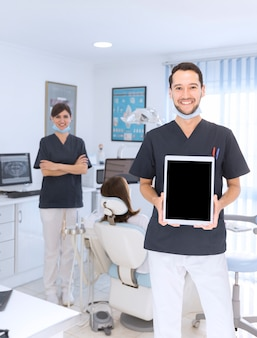 Retrato, de, macho, odontólogo, mostrando, tablete digital, em, clínica