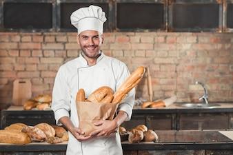 Retrato, de, macho, padeiro, segurando, loaf, de, pães, em, sacola papel