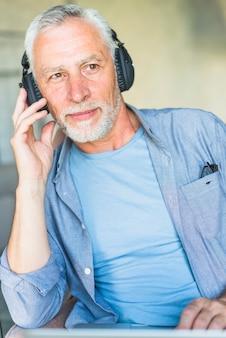 Retrato, de, macho sênior, escutar música, ligado, headphone