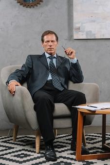 Retrato, de, maduras, homem negócios, sentando, ligado, cozy, poltrona