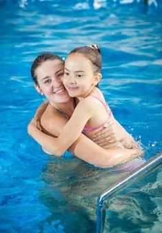 Retrato de mãe abraçando a filha na piscina