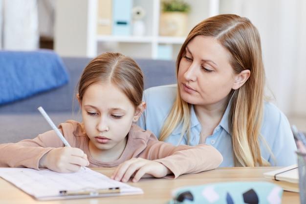 Retrato de mãe adulta amorosa, olhando para a menina bonitinha fazendo lição de casa ou teste enquanto estudava em casa em um interior aconchegante