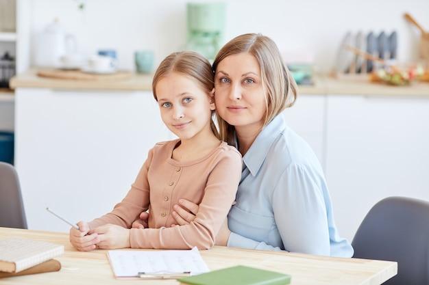 Retrato de mãe adulta amorosa posando com a filha enquanto está sentado na mesa de madeira no interior de casa e olhando para a câmera, copie o espaço