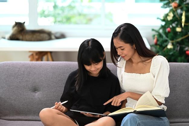 Retrato de mãe ajudando a filha a fazer o dever de casa escolar sobre tablet digital em casa. conceito de educação online.