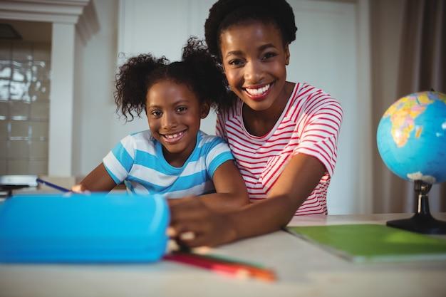 Retrato de mãe ajudando filha com lição de casa