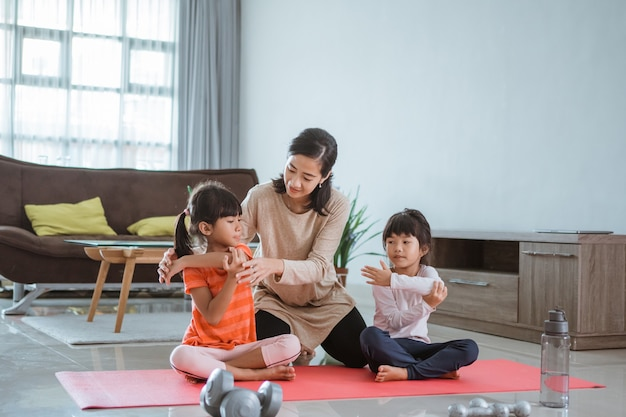 Retrato de mãe ajudando os filhos a fazerem exercícios de alongamento em casa juntos