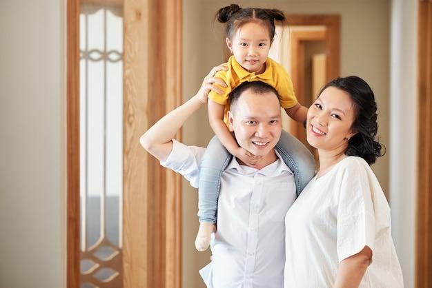 Retrato de mãe asiática sorridente feliz, pai e filha em pé no corredor do apartamento e olhando para a câmera