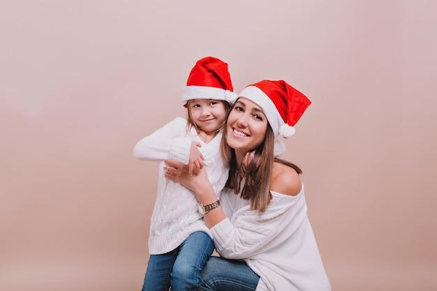 Retrato de mãe bonita com filha pequena usando pulôveres brancos e chapéus de papai noel