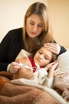 Retrato de mãe carinhosa medindo a temperatura da filha doente com termômetro digital