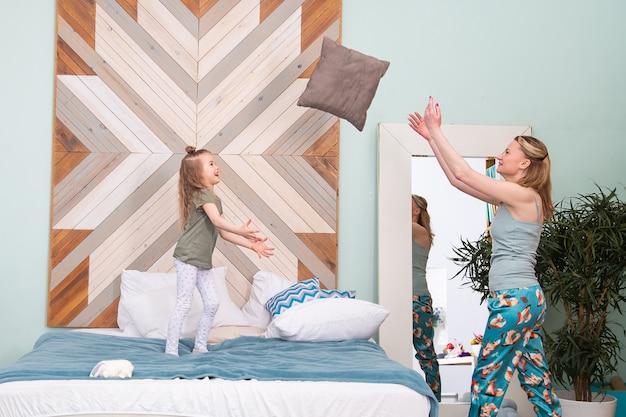 Retrato de mãe com a filha jogando travesseiros uma na outra no quarto na cama