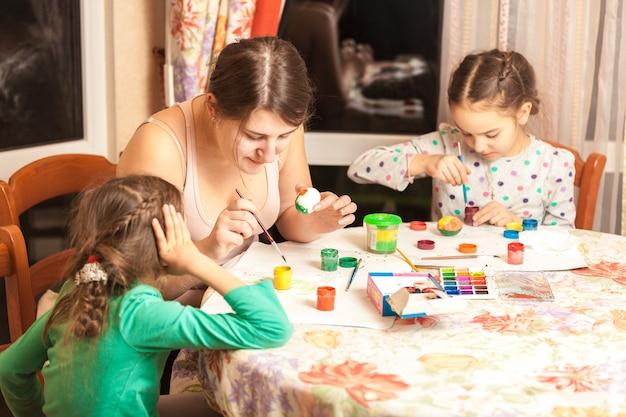 Retrato de mãe com duas filhas pintando ovos de páscoa Foto Premium
