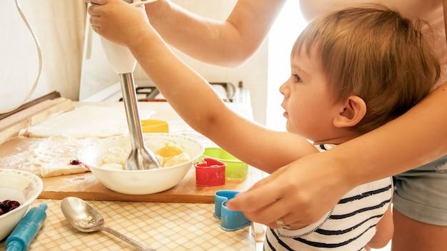 Retrato de mãe com filho de 3 anos fazendo biscoitos na cozinha pela manhã