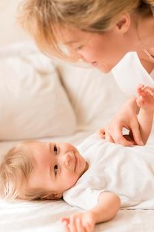 Retrato de mãe e bebê aconchegando-se na cama