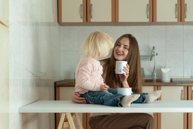 Retrato de mãe e bebê na cozinha. feliz jovem mãe e criança tomam café da manhã em casa.
