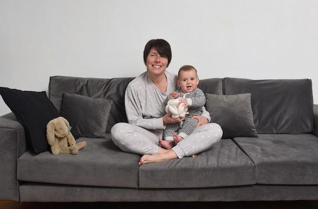 Retrato de mãe e bebê sentados no sofá de pijama