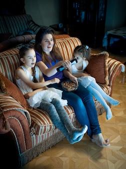 Retrato de mãe e duas filhas assistindo tv à noite no sofá